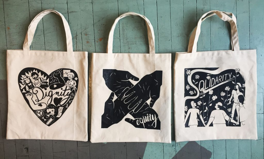 WAHC's new tote bags based on the values dignity, equity, and solidarity.