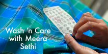 Two hands sew a label onto a blue and green madras check cloth fabric. The words: Wash 'n Care with Meera Sethi is in which text.